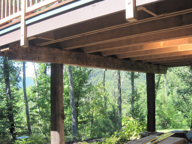 10 x 12 x 28 ft long hand hewn beam supporting deck over a patio